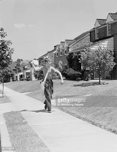 Paperboy walking along suburban street, delivering newspapers.
