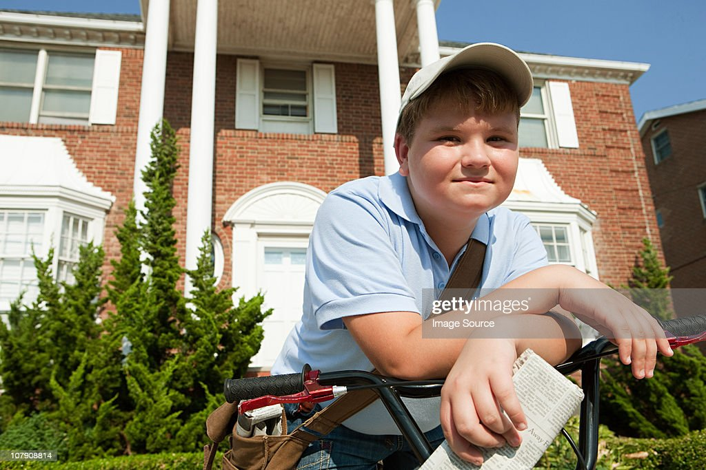 Paperboy with bike delivering newspapers : Stock Photo