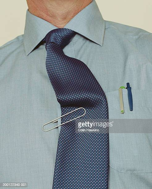 Paperclip pinning man's tie to shirt, close-up