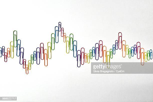 paperclips arranged in line graph - paper clips stock photos and pictures