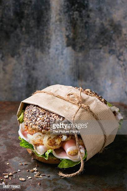 Papered Whole Grain bagel with fried onion, green salad and prosciutto ham over old rusty iron textured background.