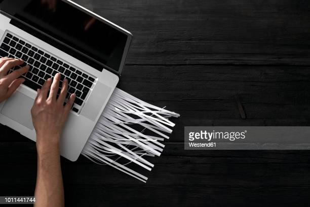 Paperless office, person using laptop on black background