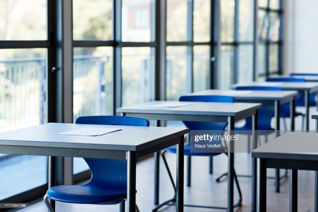 Papers on desks by window in classroom : Stockfoto
