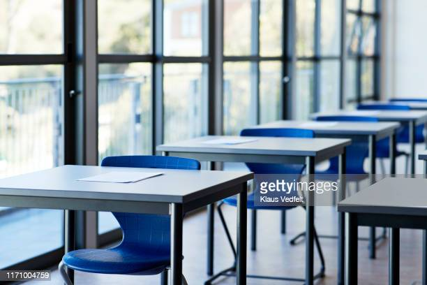papers on desks by window in classroom - education stock-fotos und bilder