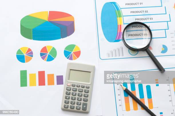 Papers with business report and magnifying glass
