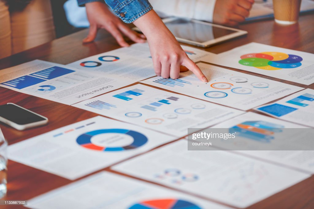 Paperwork and hands on a board room table at a business presentation or seminar. : Stock Photo