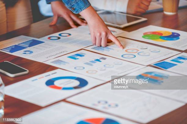 paperwork and hands on a board room table at a business presentation or seminar. - strategia foto e immagini stock