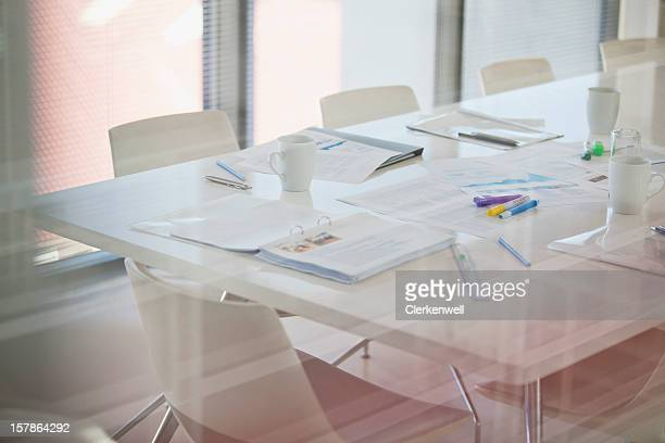Paperwork and pens on table in conference room