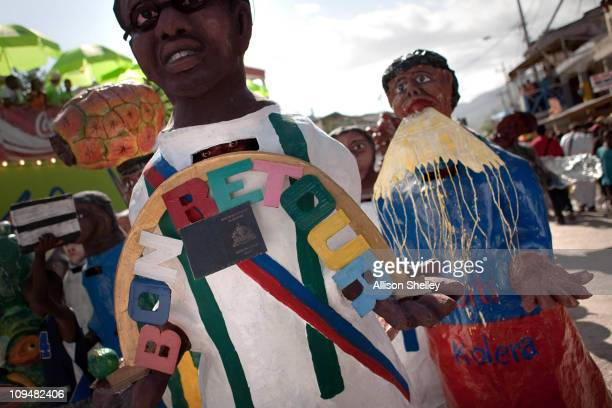 Papier mache caricatures depicting Aristide with his new Haitian passport L and a cholera victim R participate in a parade during carnival weekend on...