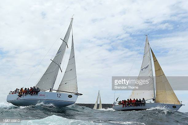 'Papillon' and 'INSX' head out to sea during the 2013 Sydney to Hobart on Sydney Harbour on December 26 2012 in Sydney Australia