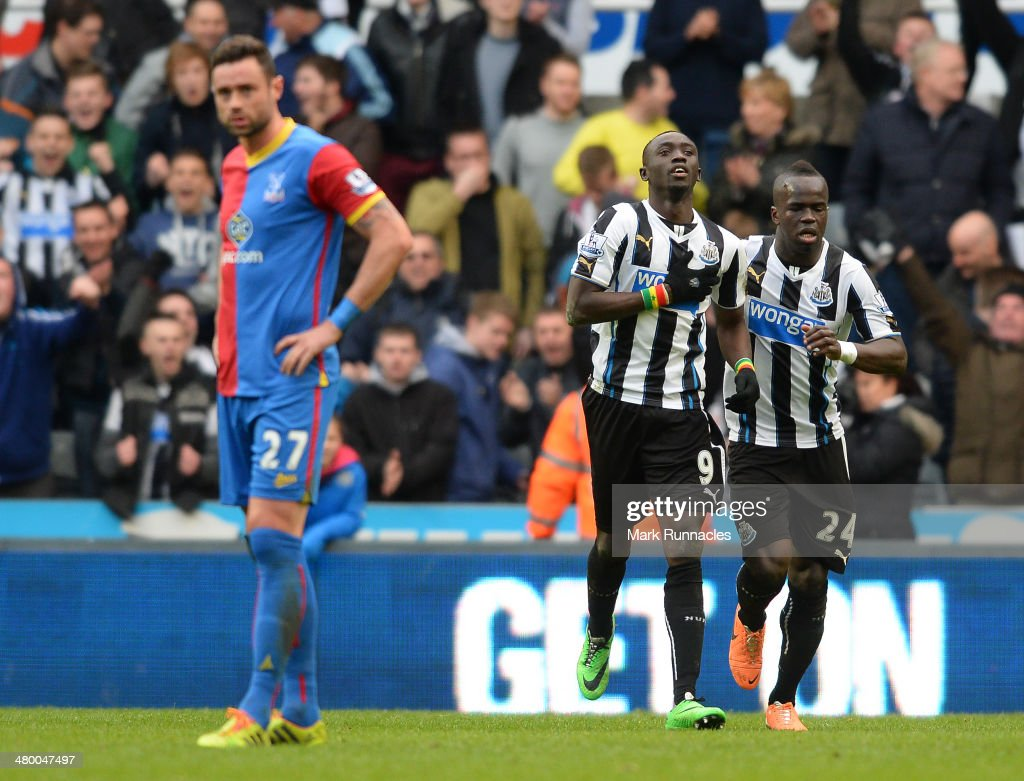 Papiss Cisse of Newcastle celebrates his last minute goal with team mate Cheick Tiote (R) during the Barclays Premier League match between Newcastle and Crystal Palace at St James Park on March 22, 2014 in Newcastle Upon Tyne, England.