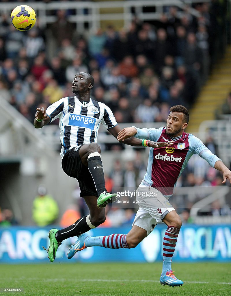 Papiss Cisse of Newcastle looks to control the ball mid flight whilst being pressured by Aston Villa's Ryan Bertrand during the Barclays Premier League match between Newcastle United and Aston Villa at St. James' Park on February 23, 2014, in Newcastle upon Tyne, England.