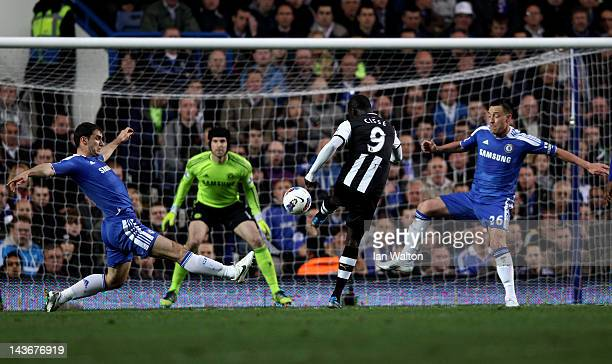 Papiss Cisse of Newcastle scores the opening goal despite the efforts from Branislav Ivanovic and John Terry of Chelsea during the Barclays Premier...
