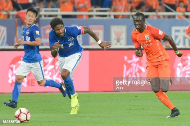 Papiss Cisse of Shandong Luneng and Eddi Gomes of Henan Jianye vie for the ball during 2017 Chinese Super League 11th round match between Shandong...