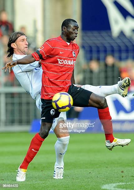 Papiss Demba Cisse of Freiburg battles for the ball with Marcelo Bordon of Schalke during the Bundesliga match between SC Freiburg and FC Schalke 04...