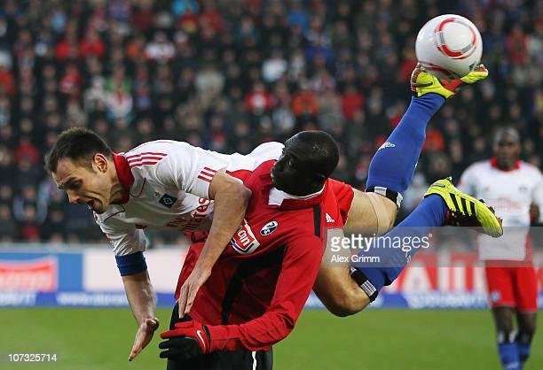 Papiss Demba Cisse of Freiburg is challenged by Heiko Westermann of Hamburg during the Bundesliga match between SC Freiburg and Hamburger SV at...