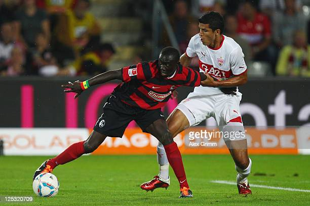 Papiss Demba Cisse of Freiburg is challenged by Maza of Stuttgart during the Bundesliga match between SC Freiburg and VfB Stuttgart at Badenova...