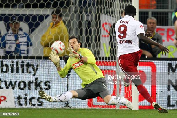 Papiss Demba Cisse of Freiburg scores his team's first goal against goalkeeper Daniel Haas of Hoffenheim during the Bundesliga match between 1899...