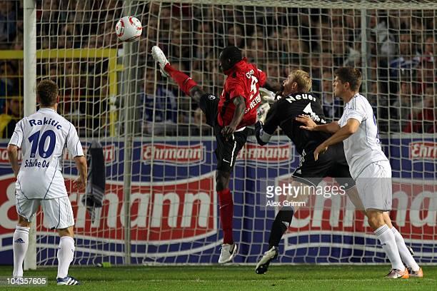 Papiss Demba Cisse of Freiburg tries to score a goal against Ivan Rakitic goalkeeper Manuel Neuer and KlaasJan Huntelaar of Schalke during the...