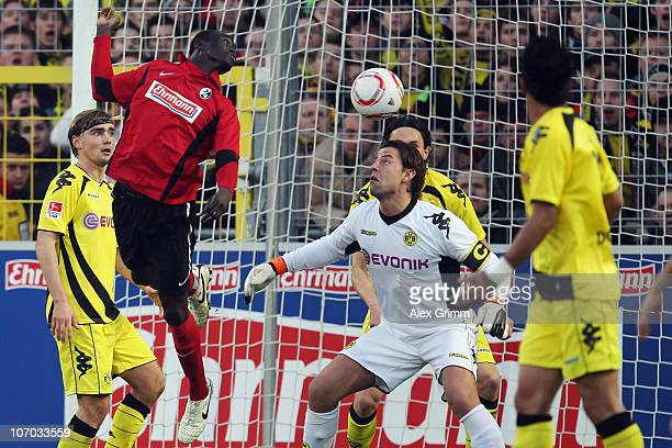 Papiss Demba Cisse of Freiburg tries to score with a header against goalkeeper Roman Weidenfeller of Dortmund before Mats Hummels of Dortmund scores...
