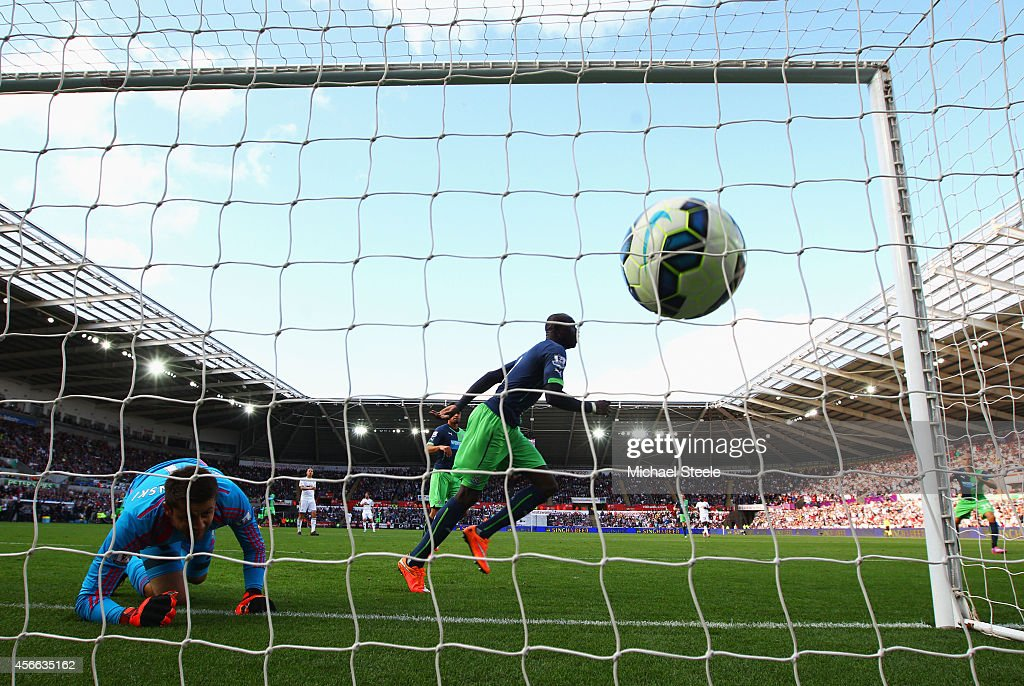 Papiss Demba Cisse of Newcastle United (R) scores their second past goalkeeper Lukasz Fabianski of Swansea City during the Barclays Premier League match between Swansea City and Newcastle United at Liberty Stadium on October 4, 2014 in Swansea, Wales.