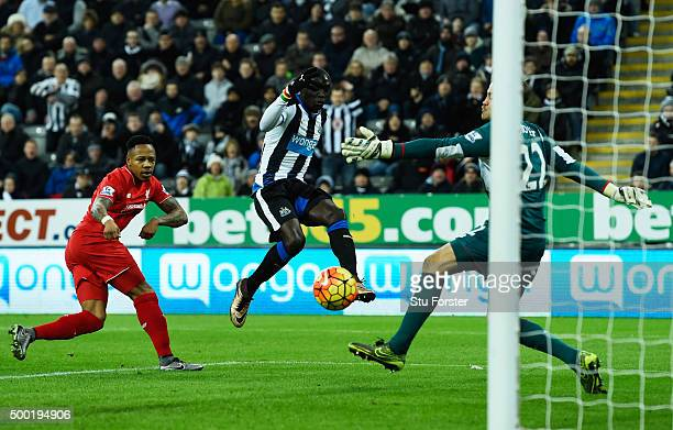 Papiss Demba Cisse of Newcastle United shoots wide as Nathaniel Clyne and goalkeeper Simon Mignolet of Liverpool look on during the Barclays Premier...