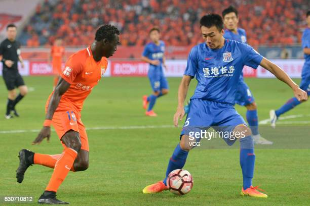 Papiss Demba Cisse of Shandong Luneng and Li Peng of Shanghai Shenhua compete for the ball during the 22nd round match of 2017 Chinese Football...