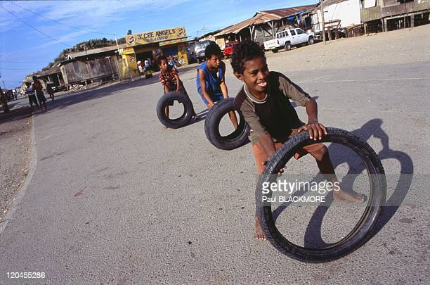 Papua in Papua New Guinea Kids play a game with tires in Hanuabada Village in Port Moresby