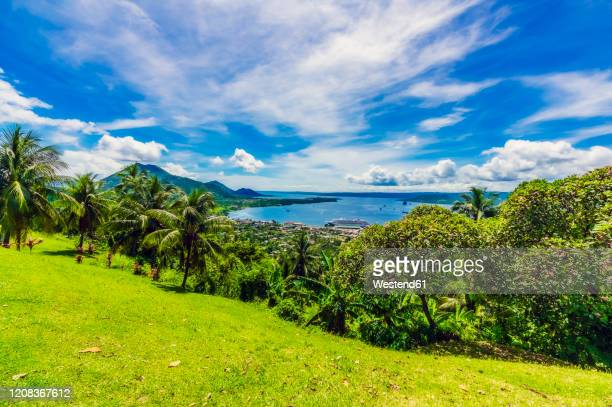 papua new guinea, east new britain province, rabaul, clouds over palm trees growing on green hillside of new britain island - papua new guinea stock pictures, royalty-free photos & images