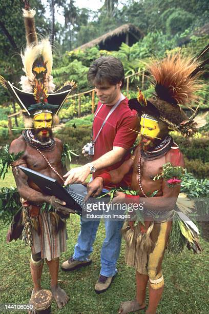 Papua New Guinea Huli Wigmen Using A Laptop With Tourist