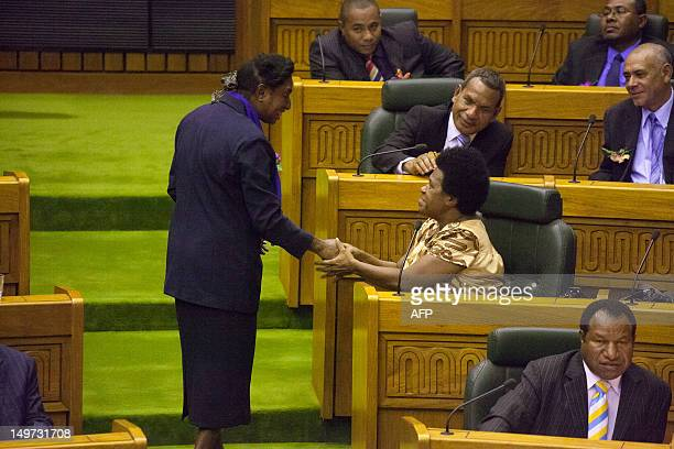 Papua New Guinea parliamentarians Loujaya Toni and Delilah Gore shake hands in Port Moresby on August 3 2012 Peter O'Neill was reelected the next...