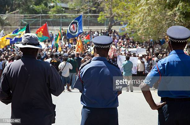 Papua New Guinea police officers watch on as hundreds of students marched towards the university gate in Port Moresby on August 2 during a protest...