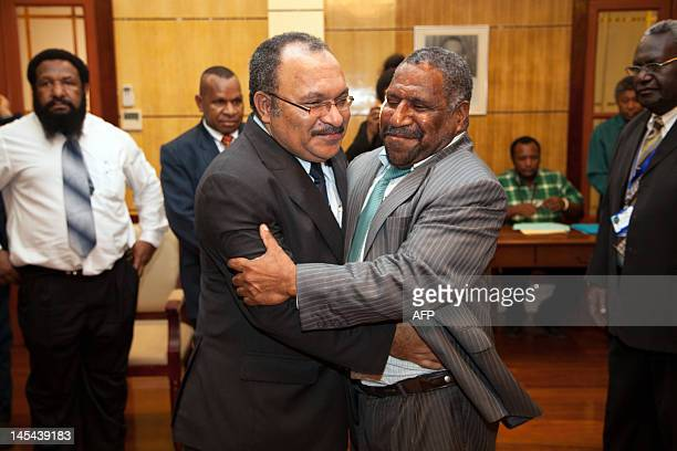 Papua New Guinea Prime Minister Peter O'Neill and Parliament Speaker Jeffrey Nape embrance after an almost four hour delay in signing documentation...