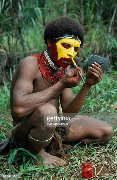 Papua New Guinea Southern Highlands Tari Valley Huli tribesman painting his face using old car wing mirror to see his reflection