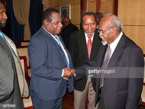 Papua New Guinean Prime Minister Michael Somare shakes hands with his ministers at Government House in Port Moresby on December 14 2011 Michael...