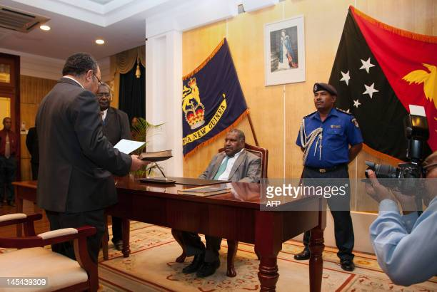 Papua New Guinea's Peter O'Neill takes the swearing in oath as Parliament Speaker and acting GovernorGeneral Jeffrey Nape looks on after signing...