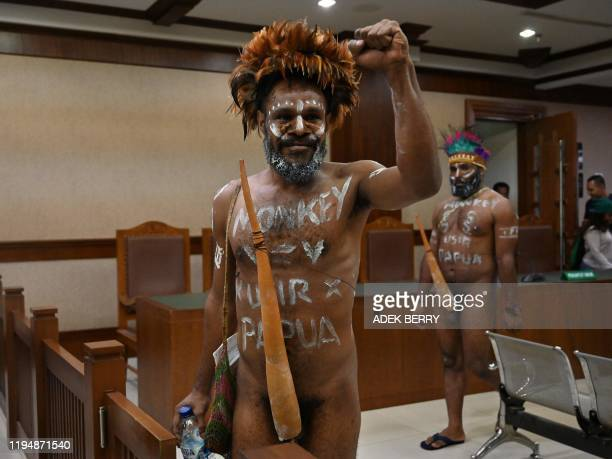 Papuan activist Ambrosius Mulait gestures as he and Dano Anes Tabuni walk into a courtroom prior to their trial at the Central Jakarta court in...