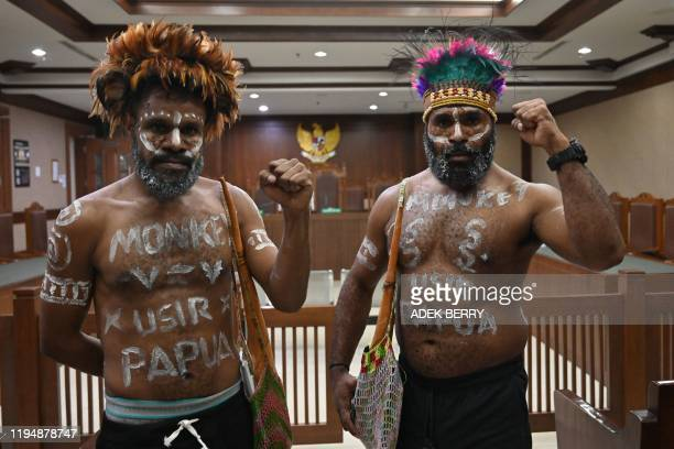 Papuan activists Dano Anes Tabuni and Ambrosius Mulait gesture prior to their trial inside the Central Jakarta court in Jakarta on January 20 2020...