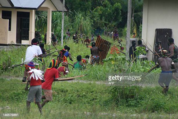 Papuan tribal warriors armed with bows and arrows and improvised shields joined by minors from Amole village clash with tribes from Harapan village...