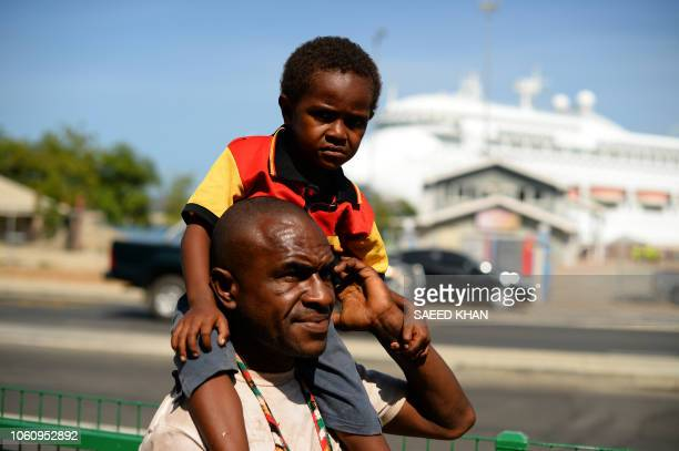 A Papuan villager carries his child on shoulders in downtown Port Moresby on November 13 ahead of the AsiaPacific Economic Cooperation summit in Port