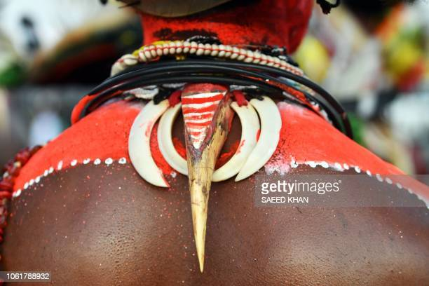A Papuan villager of the Hela tribe clad in traditional costume performs before the arrival of China's President Xi Jinping at the airport in Port...