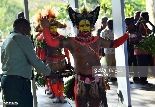 TOPSHOT Papuan villagers in traditional costume go through the security screening at Parliament House in Port Moresby on November 16 ahead of...