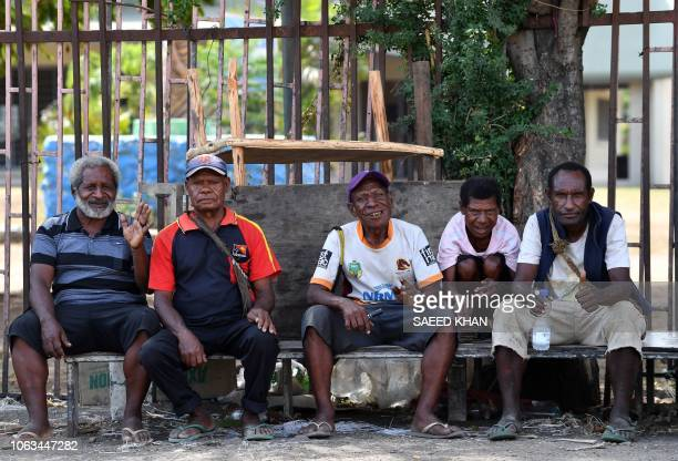 Papuan villagers sit outside a women's only makeshift market on the outskirts of Port Moresby on November 19 one day after the AsiaPacific Economic...