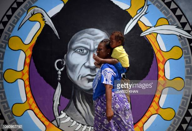 Papuan woman walks in front of a mural in downtown Port Moresby on November 13 ahead of the AsiaPacific Economic Cooperation summit in Port