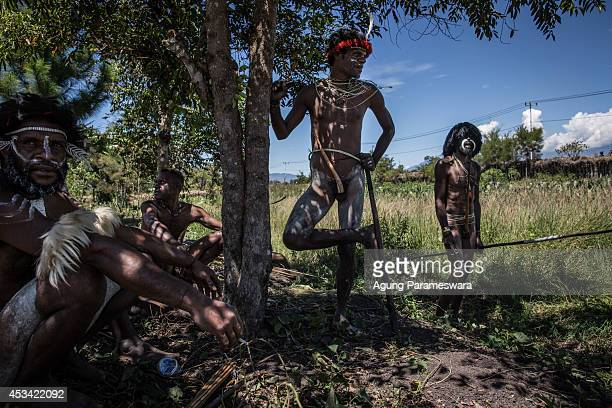 Papuanese tribal men rest in the shade as they finished their performances during the 25th Baliem Valley festival on August 8, 2014 in Wamena,...