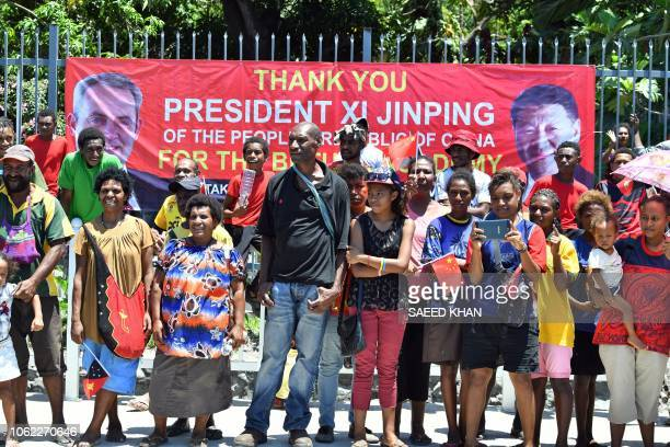Papuans gather at the roadside to welcome China's President Xi Jinping in Port Moresby on November 16 ahead of the AsiaPacific Economic Cooperation...