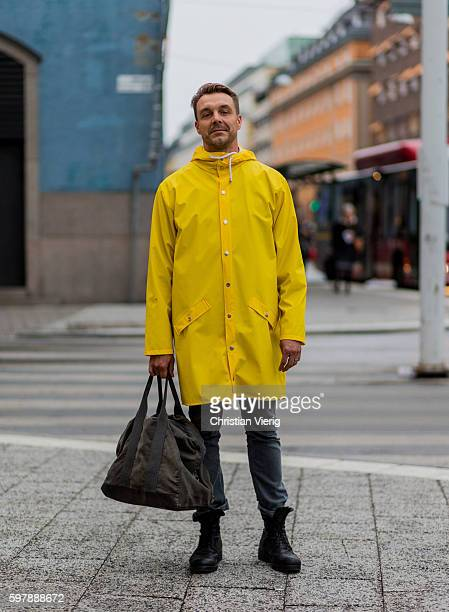 Par Bauer wearing a yellow rain coat weekender bag and black boots outside By Malina during the first day of the Stockholm Fashion Week Spring/Summer...