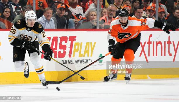 Par Lindholm of the Boston Bruins skates the puck against Kevin Hayes of the Philadelphia Flyers on March 10, 2020 at the Wells Fargo Center in...