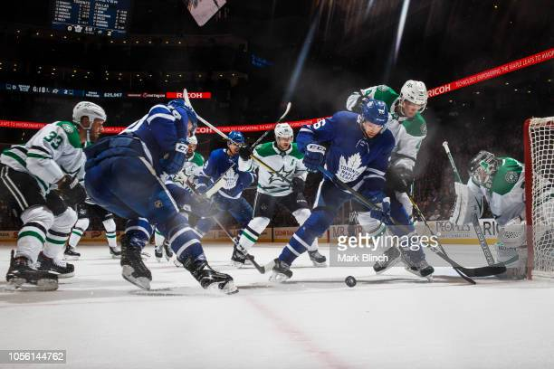 Par Lindholm of the Toronto Maple Leafs and Morgan Rielly battle against Marc Methot of the Dallas Stars Miro Heiskanen and Anton Khudobin during the...