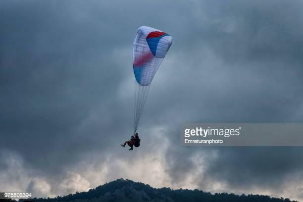 para glider coming down on an overcast day at ölüdeniz,fethiye. - emreturanphoto - fotografias e filmes do acervo